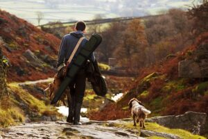 man and dog on shoot in countryside